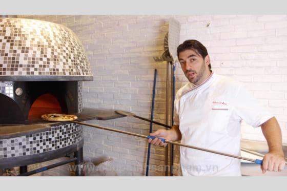 Một đầu bếp đang nướng món bánh Pizza